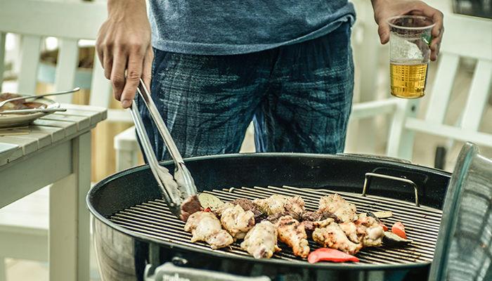 ビールを片手にバーベキューで肉を焼いている男性