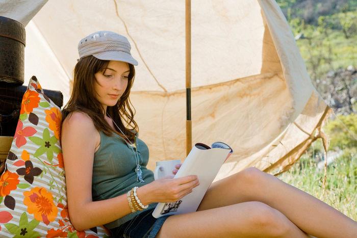 テントサイトで本を読む女性