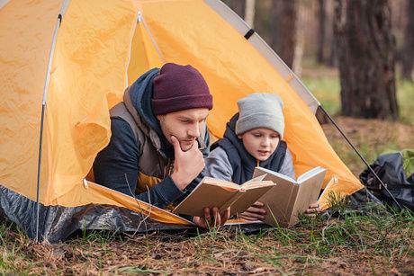 テントから並んで顔を出し読書をする親子