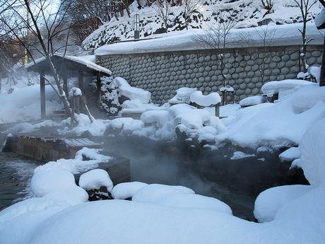 雪の積もった間に見える温泉