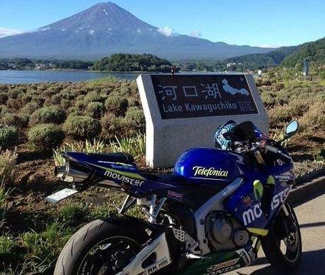 富士山を背景に河口湖の案内の前に止められているバイク