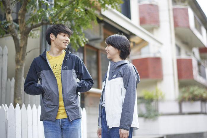 ミレーのジャケットを着て会話をしている男女