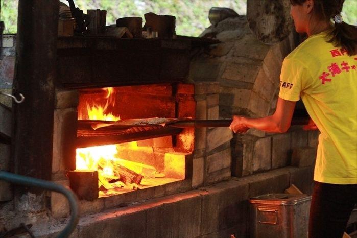 ピザ釜でピザ作りをする人