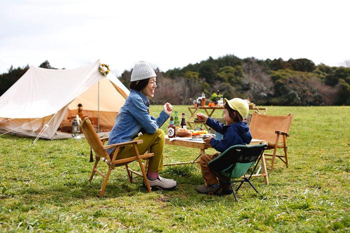 芝生の上で椅子に座って食事をする親子