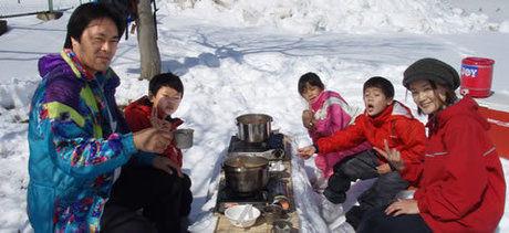 冬の大佐山オートキャンプ場でスノーピクニックをする家族