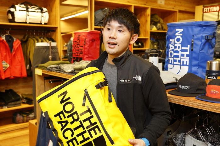 黄色いリュックを紹介している店員