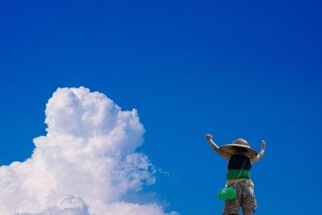 夏空で万歳をする少年