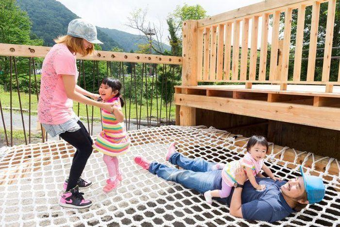 丸沼高原わんぱく砦のアスレチックで家族が遊んでいる写真