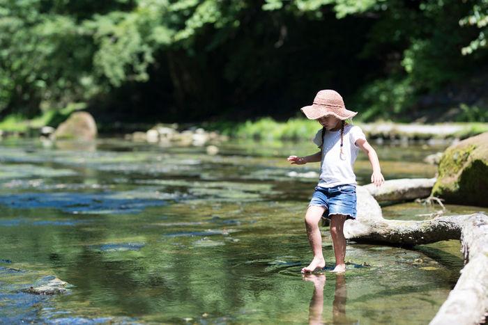 川に足を入れている少女