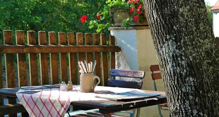外の机に敷かれたテーブルクロスとその上に置かれたマグカップに入った食器と塩胡椒