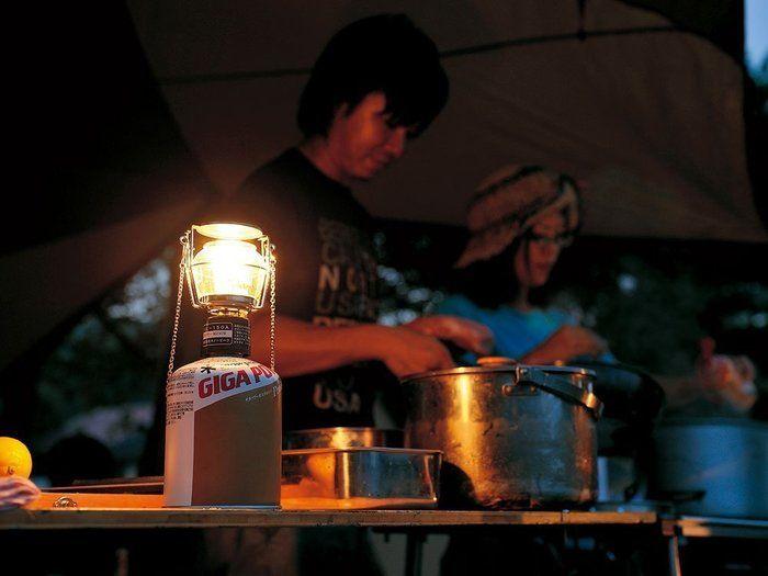 キャンプでランタンを使って調理をしている女性たち