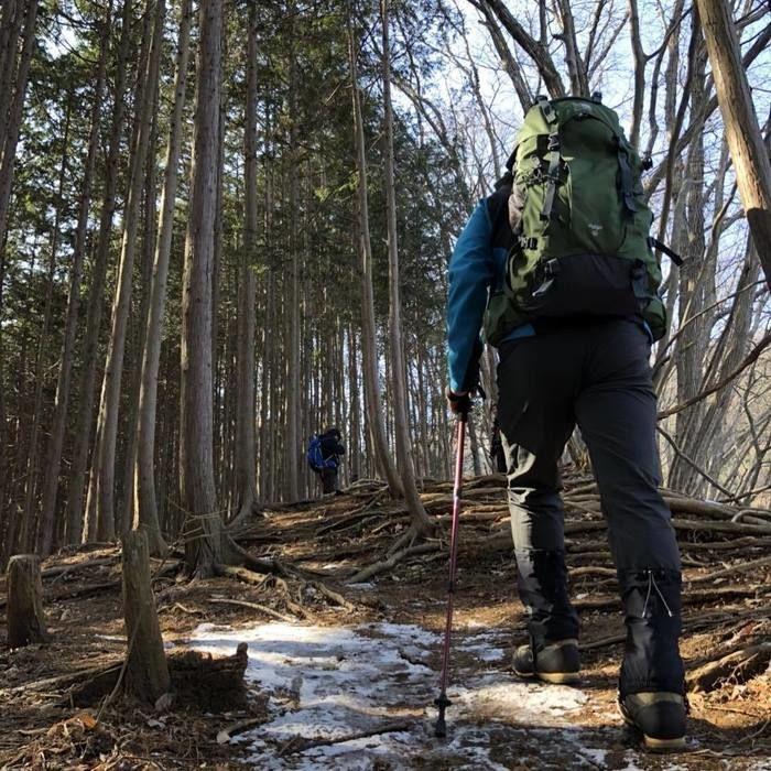 カリマーのバックパックで山道を歩いている人