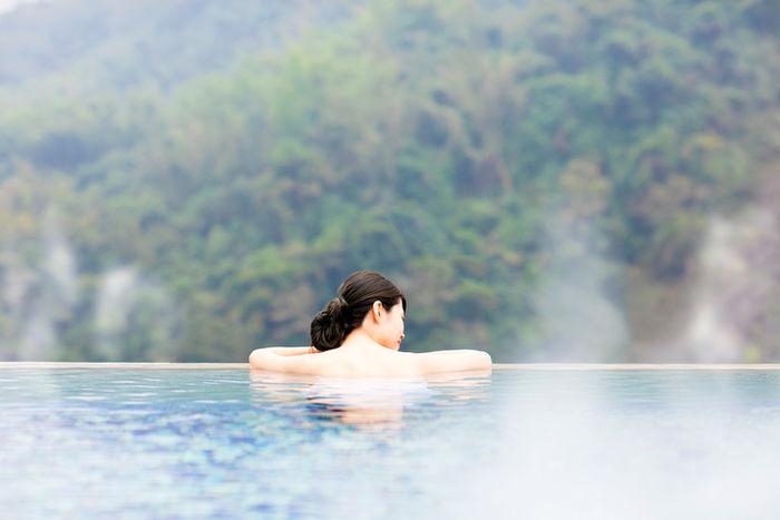 温泉に浸かる背中を向けた女性