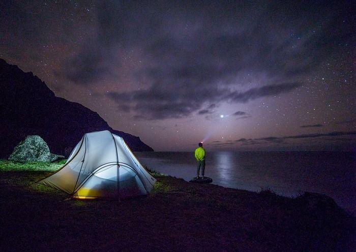 夜の湖の淵辺で湖を眺める男性とテント内の明かりを灯している石油ストーブ