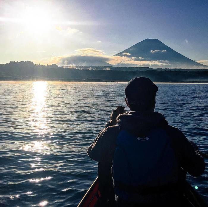 湖で太陽の方向に佇む男性