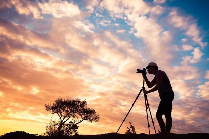 夕暮れの中写真を撮る男性