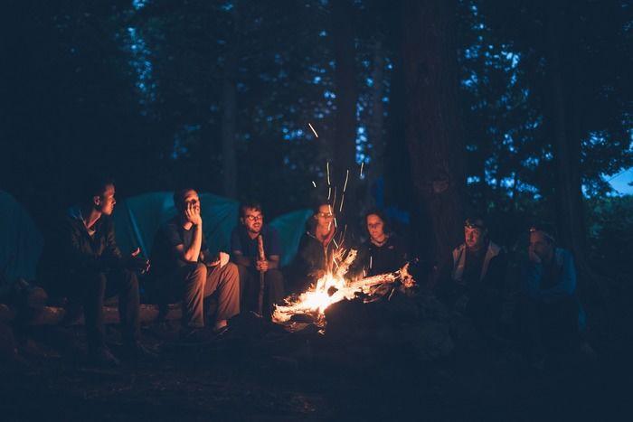 夕暮れにたき火を囲む人々