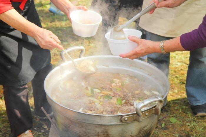 青根キャンプ場で大きな鍋で作ったスープをお椀に注いでいる様子
