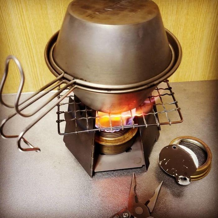 シェラカップを上下に挟み火にかけ、料理をしている様子