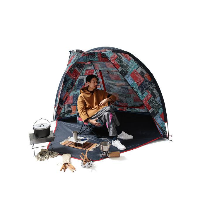 バンダナ柄のテント内でくつろぐ男性