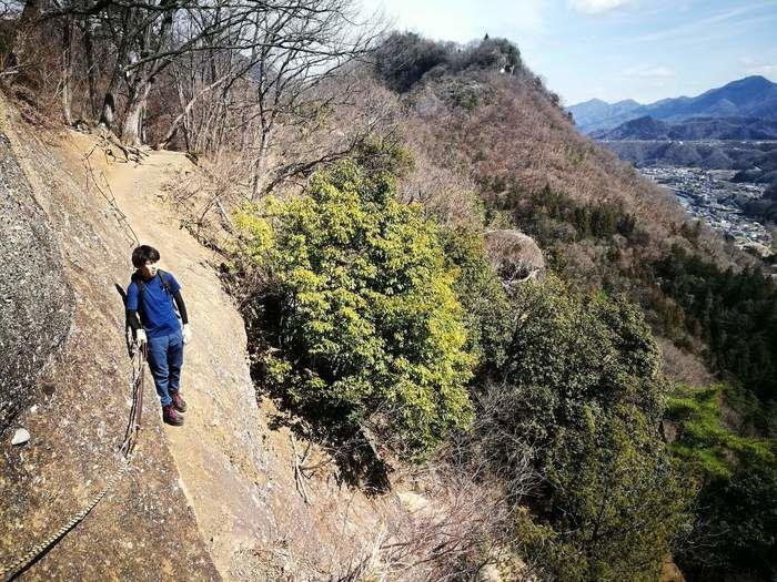 岩殿山の岩の崖を歩く人