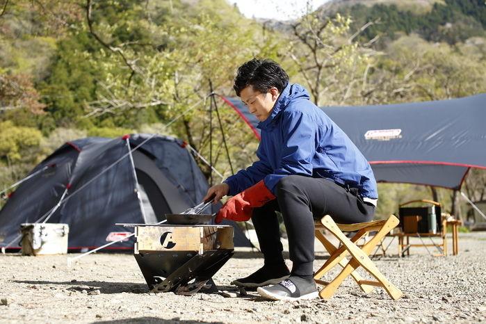 椅子に座りローコンロで料理をする男性