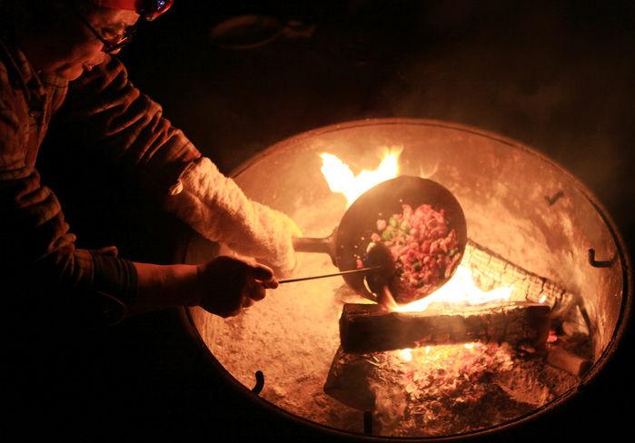 中華鍋と炭を使ったキャンプでの料理の様子