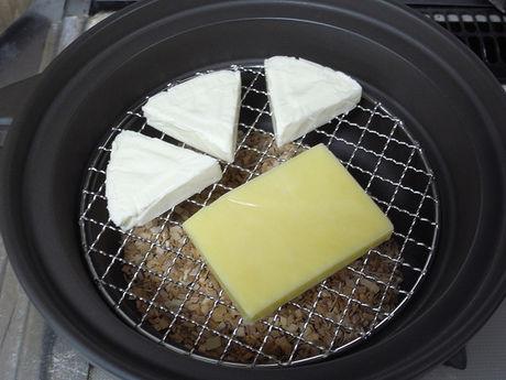 カマンベール入りのプロセスチーズと、ゴーダチーズを中華鍋を使い燻製する様子
