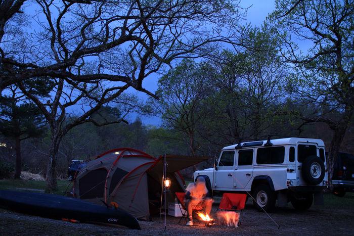 夕暮れ時のキャンプで火を扱っている人