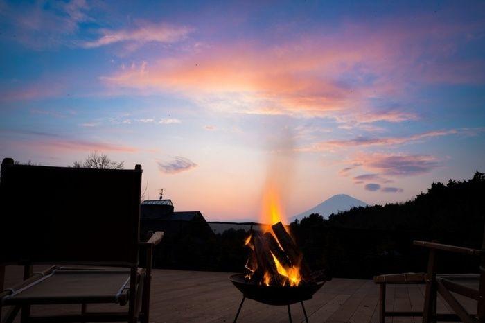 焚き火とその後ろに映る富士山の景観