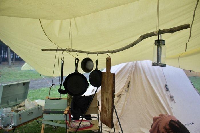 タープ内に吊るした流木と張り網で作られた収納スポット