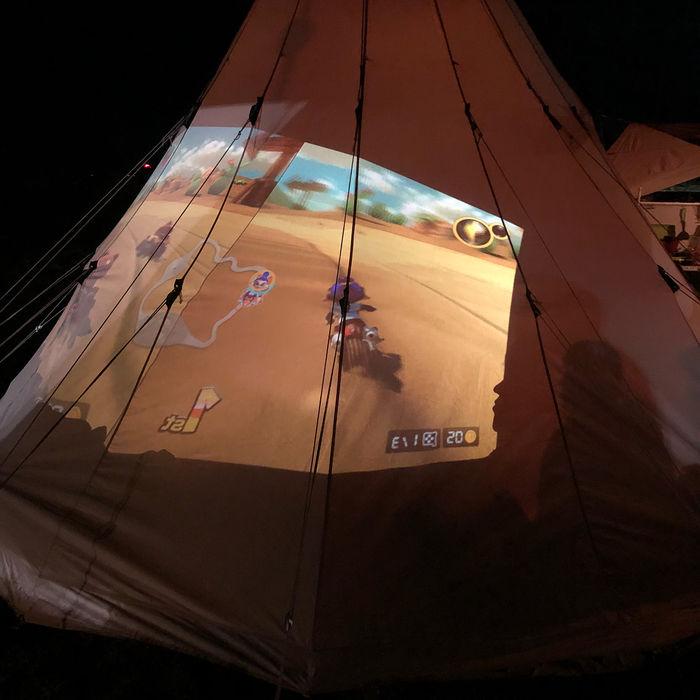 テントに任天堂スイッチを写し、ゲームをしている様子