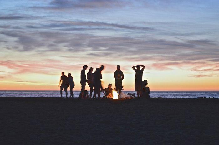 浜辺でたき火を囲む人々