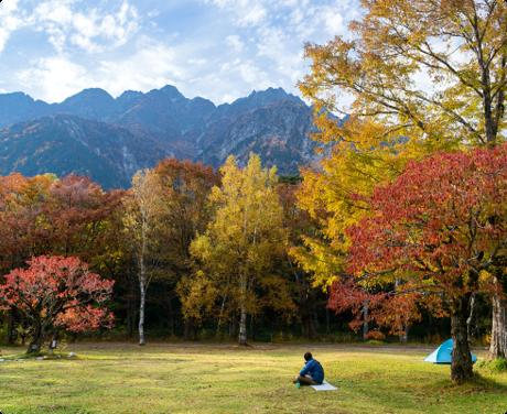 紅葉の美しい公園でくつろぐ男性