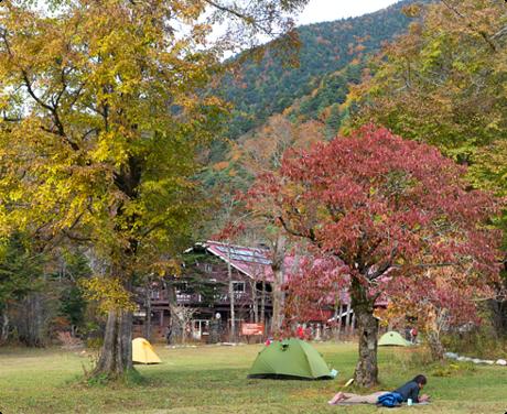 徳澤園キャンプ場で芝生に寝転ぶ男性