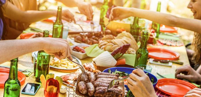 肉やサラダのごちそうに皆が手を伸ばす様子