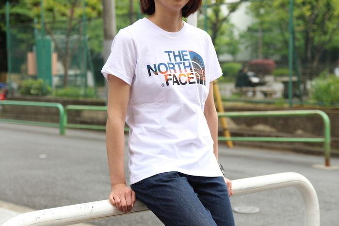 ノースフェイスのTシャツを着て座っている女性