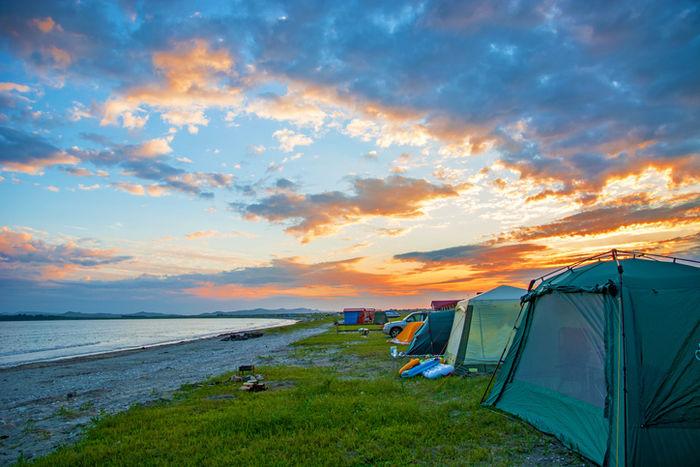 夕暮れの海沿いのキャンプサイトの写真