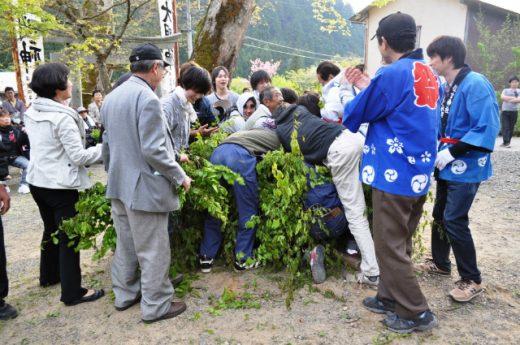 神宿る森を担ぎ花奪う、男たち