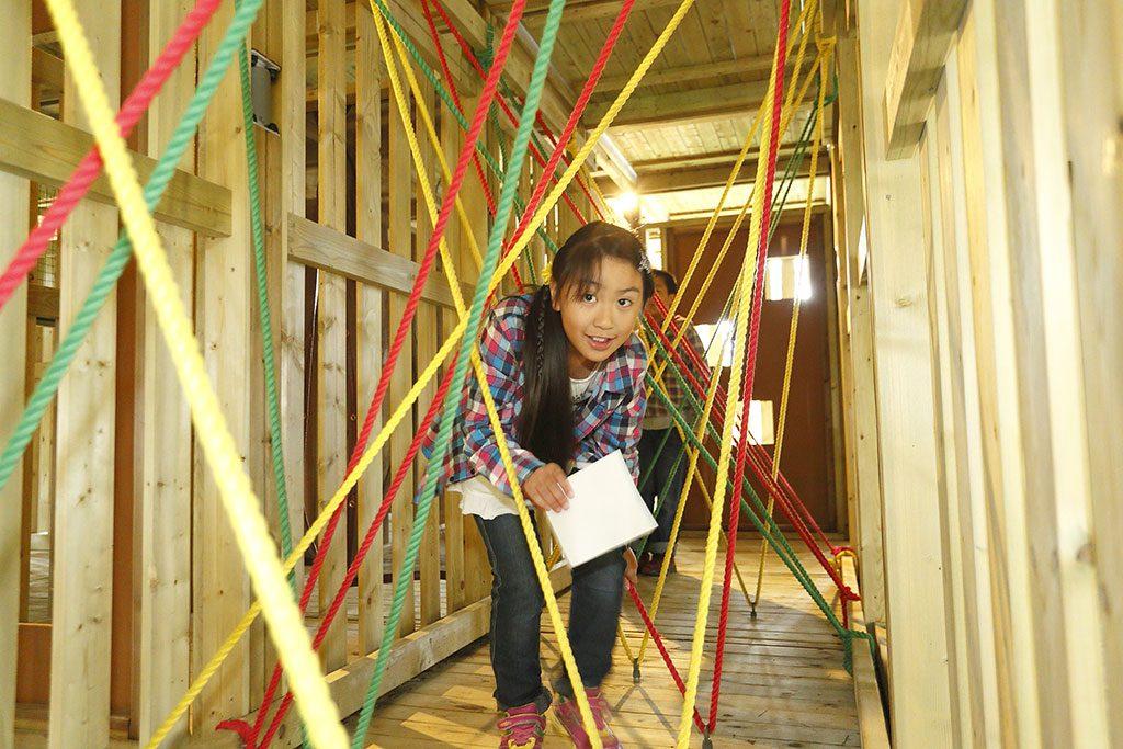 立体迷路でロープをくぐる子ども/富士すばるランド(山梨県富士河口湖町)
