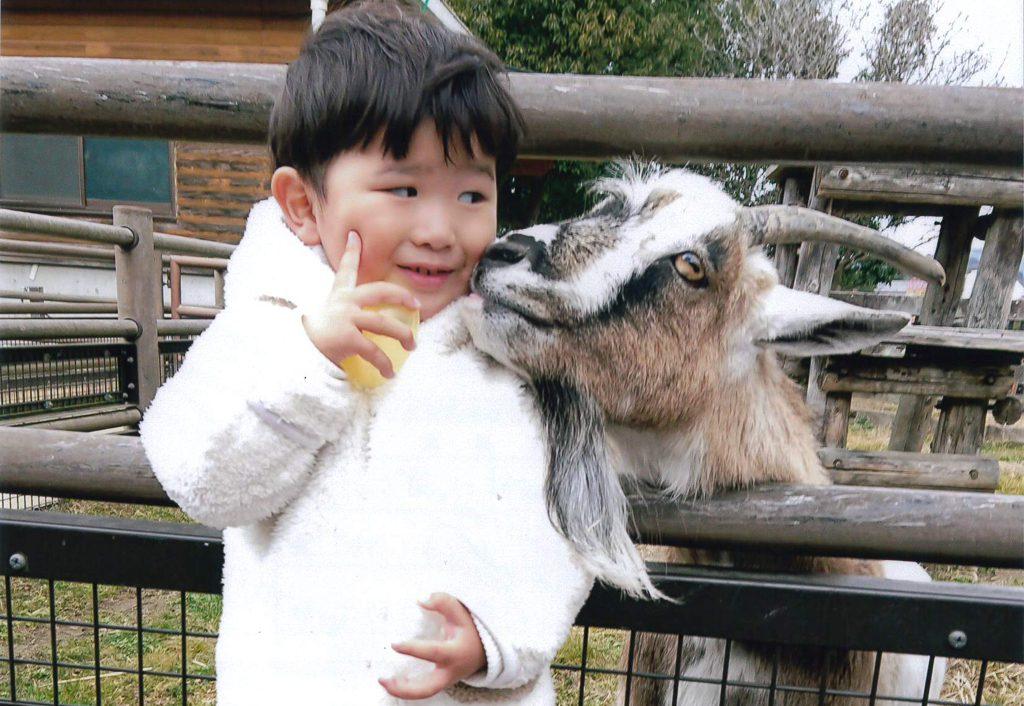 ヤギと写真を撮る子ども/福山市立動物園(広島県/福山市)