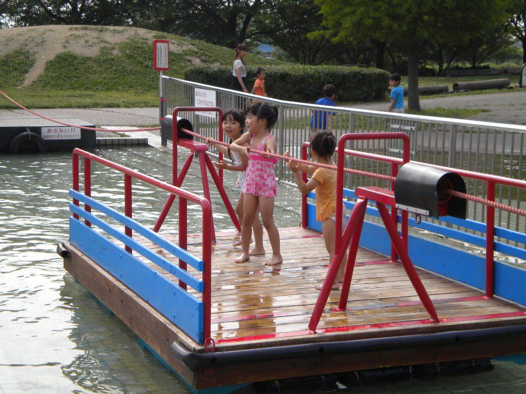 水に浮かぶ木製いかだに乗る子どもたち/とだがわこどもランド(愛知県名古屋市)