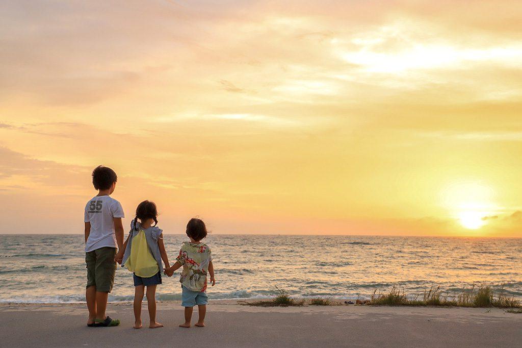 砂浜で夕日を見ている子供たち