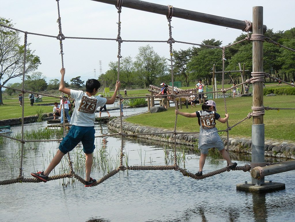 水上のネットを進む子どもたち/鬼怒グリーンパーク水上アスレチック(栃木県/高根沢町)