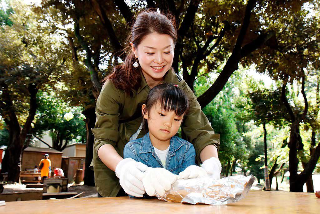 さつまいもをアルミホイルで包む親子/羽根木プレーパーク(東京都/世田谷区)