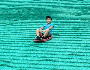 ソリで人工芝を滑る子ども/舎人公園(東京都/足立区)