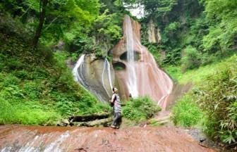赤い岩肌を流れる嫗仙の滝、岩肌には穴が見える