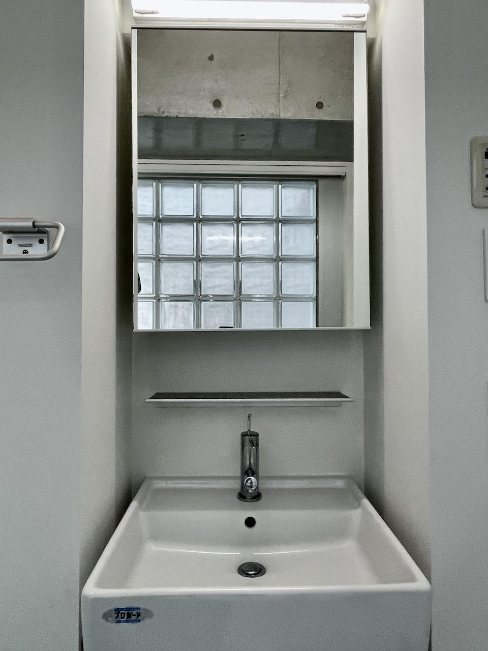 洗面所。後ろにまた光が入るガラスブロックが。