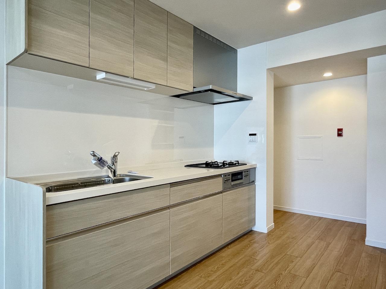 システムキッチン。奥には冷蔵庫置場と棚。