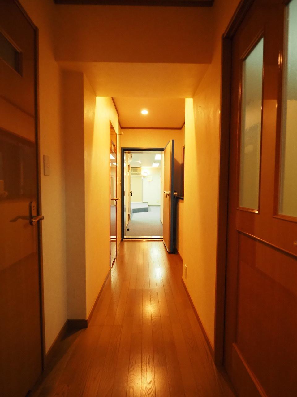 この普通のマンションの廊下の奥に見えるスタジオが異彩です。